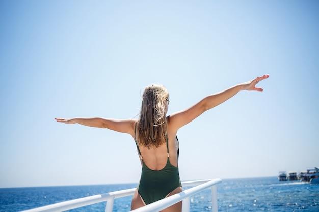 Une fille avec une belle silhouette en maillot de bain vert. elle est sur un yacht blanc dans la mer rouge