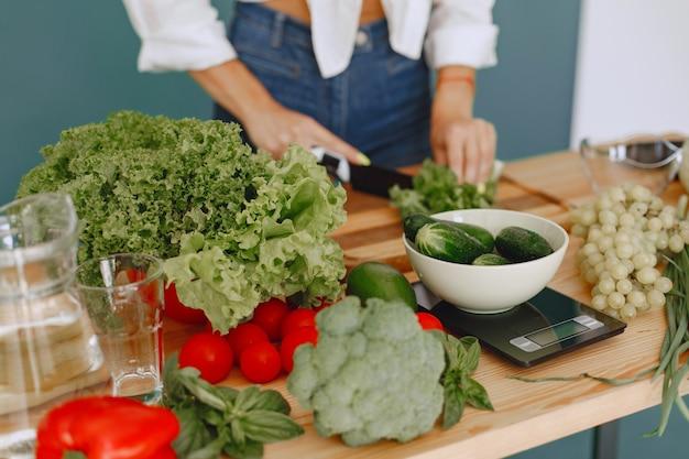 Fille belle et sportive dans une cuisine avec un légumes