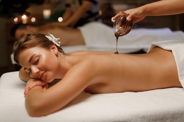 Une fille bénéficiant d'un massage balinais avec du chocolat