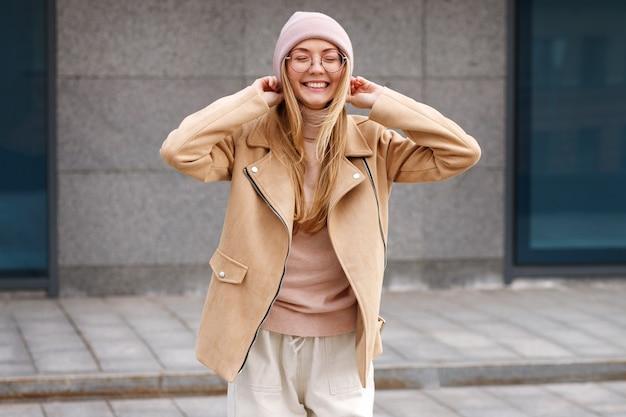 Fille avec un bennie rose dans le vent souriant joyeusement dans la rue