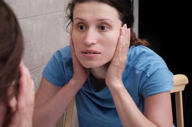 Une fille avec des béquilles se lave le visage devant le miroir de la salle de bain. rééducation après une fracture.