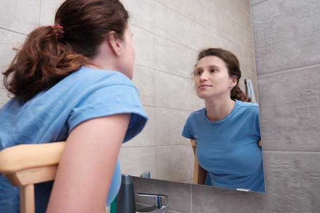 Une fille avec des béquilles se regarde dans le miroir de la salle de bain. rééducation après une fracture.