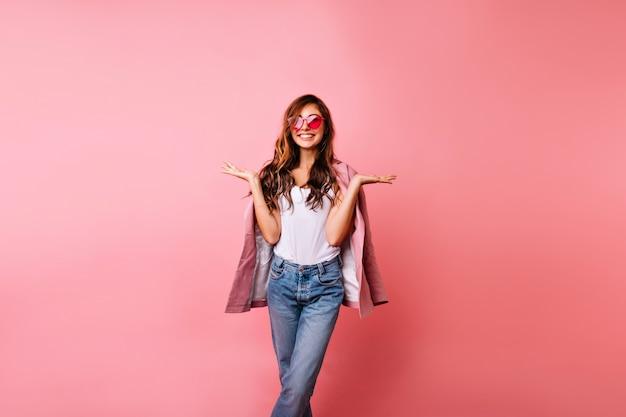 Fille bien habillée positive debout sur rose avec sourire. femme au gingembre aux cheveux longs sans soucis, profitant de son temps libre.