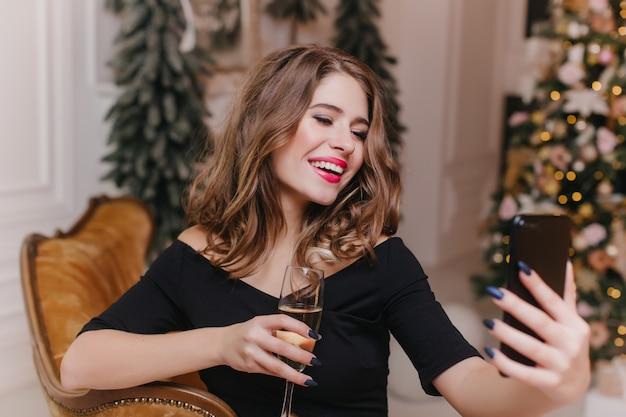 Fille bien habillée tenant un téléphone noir et prenant une photo d'elle-même. charmante femme brune avec verre à vin à l'aide de smartphone pour selfie avec arbre de noël sur le mur.