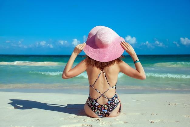 Une fille en bikini et chapeau rose, photo de dos. jeune femme se faire bronzer sur une plage. belle femme posant à la plage de sable d'été. portrait d'été en plein air de jolie femme de style sport au chapeau.
