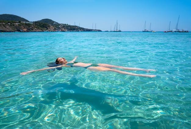 Fille de bikini d'ibiza nageant une plage claire