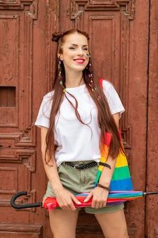 Fille bisexuelle en vêtements colorés posant sur la vieille porte