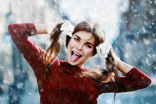 Fille blague blague à la caméra dans la neige