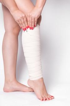 Fille sur un blanc corrige un bandage élastique qui lie