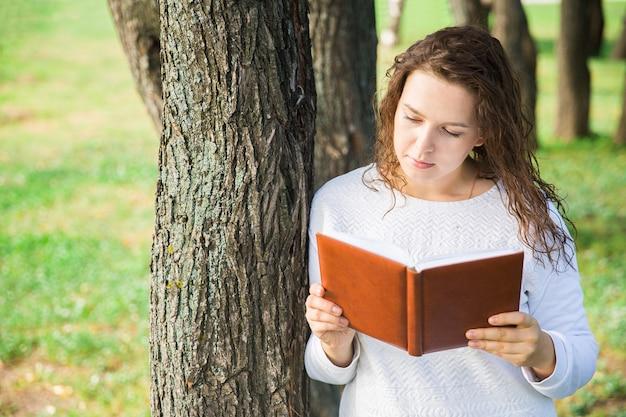 Fille en blanc avec un livre brun dans le parc. lecture en forêt