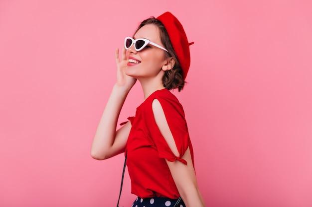 Fille blanche heureuse avec une coiffure courte élégante souriante. modèle féminin français à la mode exprimant des émotions positives.
