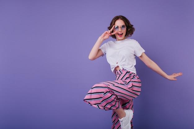 Fille blanche rêveuse dans des baskets élégantes sautant sur un mur violet. debonair femme aux cheveux courts en lunettes de soleil s'amuse pendant la séance photo.