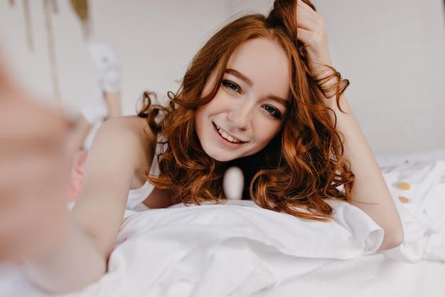 Fille blanche sensuelle avec une coiffure ondulée faisant selfie le matin. jolie jeune femme allongée sur le lit et prendre une photo d'elle-même.