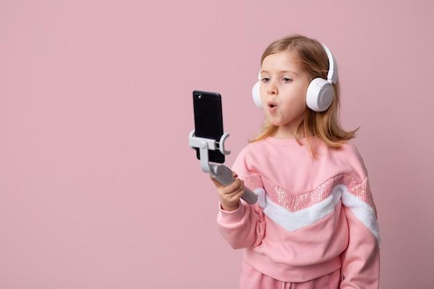 Fille blogueuse écoute de la musique avec un casque blanc
