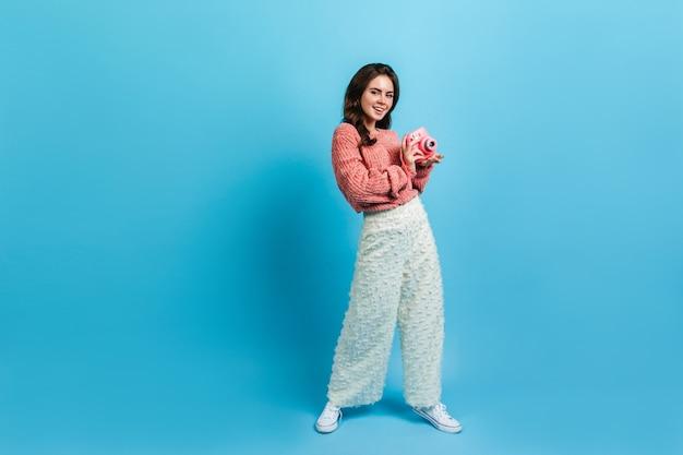 Fille de blogueuse élégante posant avec appareil photo instax rose. dame en jupe-culotte blanche sourit doucement sur le mur bleu.