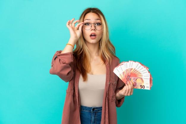 Fille blonde adolescente prenant beaucoup d'euros sur fond bleu isolé avec des lunettes et surpris