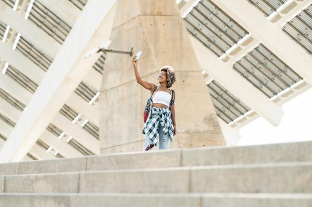 Fille blonde afro, sac à dos dans la ville, prend selfie, voyageuse