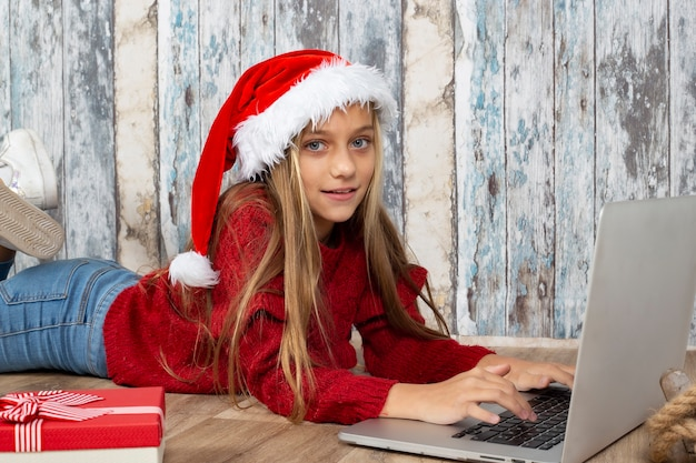 Fille blonde à l'aide d'un ordinateur portable à noël pour communiquer