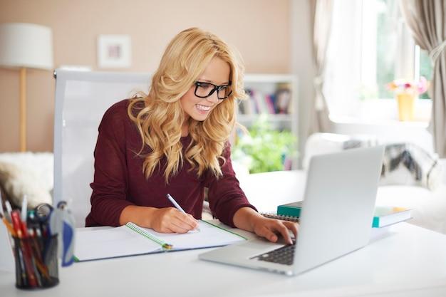 Fille blonde à l'aide d'un ordinateur portable pendant ses études à la maison