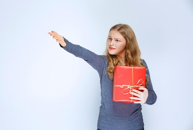 Une fille blonde a l'air insatisfaite et retourne sa boîte cadeau rouge.