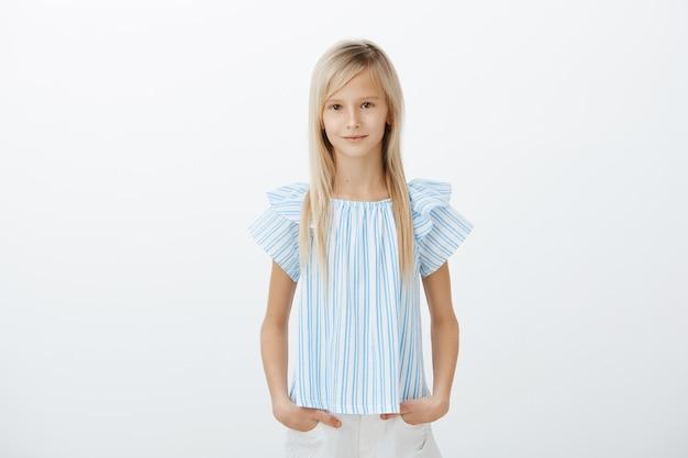 Fille blonde à l'air sérieux confiant dans des vêtements bleus, tenant les mains dans les poches et souriant largement pendant l'audition des enfants, être sûr de lui et détendu sur un mur gris