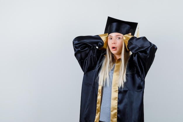 Fille blonde en appuyant sur les mains sur les oreilles en robe de graduation et casquette et à la surprise