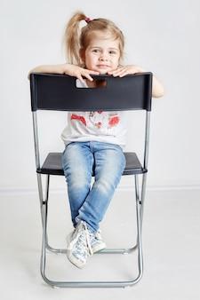 Fille blonde assise dans la chaise du directeur