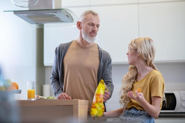 Une fille blonde assise dans la cuisine et parlant à son père