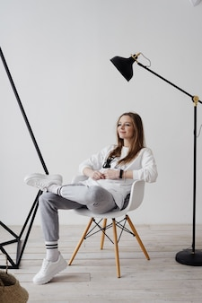 Fille blonde assise sur un fauteuil à la maison dans l'atmosphère de travail, le travail à domicile, la joie d'être à la maison