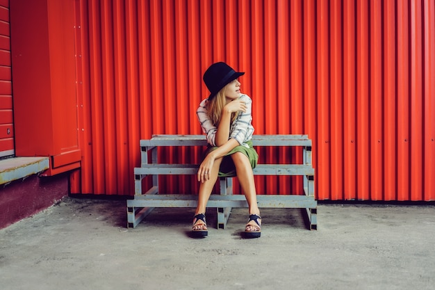 Fille blonde au chapeau. photo de rue. une belle fille portant des vêtements décontractés sourirait mystérieusement. style vintage
