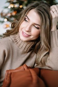 Fille blonde aux cheveux longs dans une robe tricotée marron