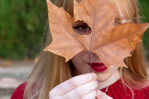 Fille blonde aux lèvres peintes et pull rouge couvrant un œil avec une feuille d'arbre.