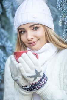 Une fille blonde aux yeux bleus tient une boisson chaude dans des gants par une journée d'hiver glaciale à l'extérieur.