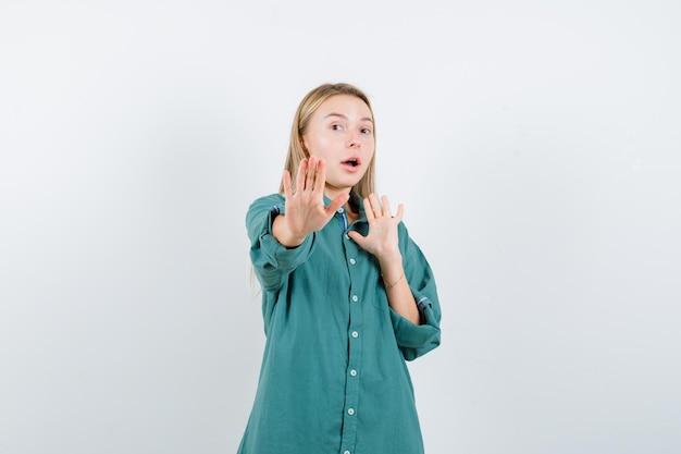 Fille blonde en blouse verte montrant des panneaux d'arrêt et à la surprise