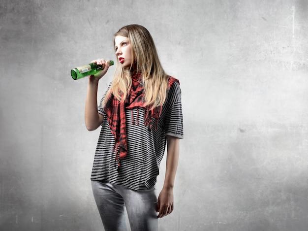 Fille blonde buvant de la bière
