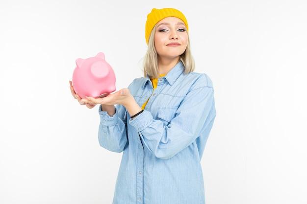 Fille blonde caucasienne dans une chemise bleue est titulaire d'une tirelire rose avec copie espace