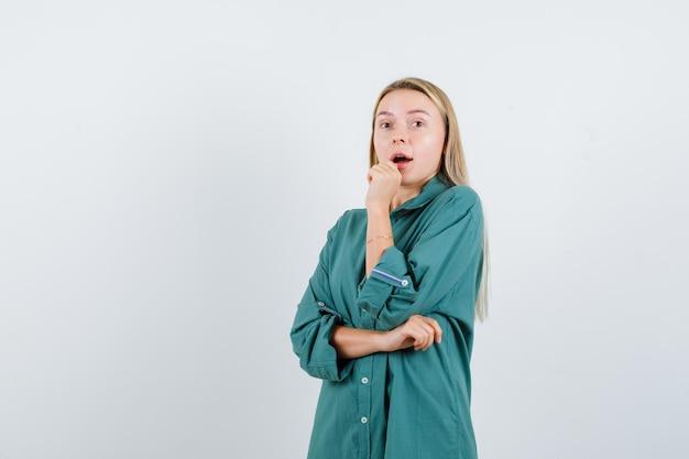 Fille blonde en chemisier vert serrant le poing, ouvrant la bouche tout en tenant la main sur le coude et l'air surpris