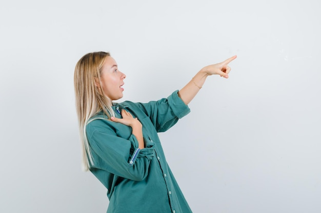 Fille blonde en chemisier vert tenant la main sur la poitrine tout en pointant vers la droite et l'air surpris
