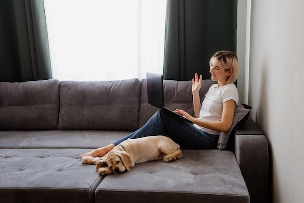 Fille blonde avec un chien assis sur le canapé avec un espace pour ordinateur portable pour le texte