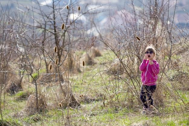 Fille blonde confuse debout seul parmi les buissons secs et appelant à l'aide