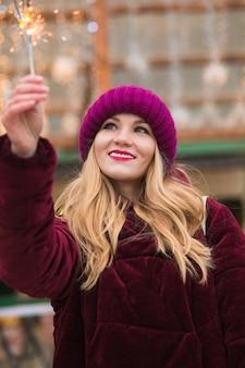 Fille blonde cool vêtue de vêtements élégants, tenant des cierges magiques lumineux à la foire de noël à kiev