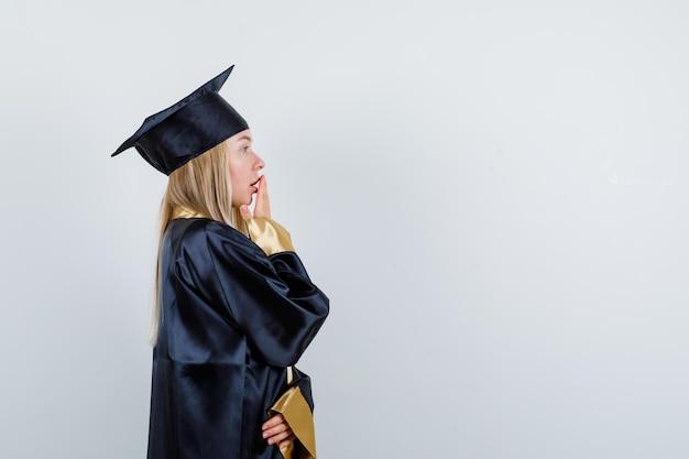 Fille blonde couvrant la bouche avec la main dans la robe de graduation et la casquette et à la surprise
