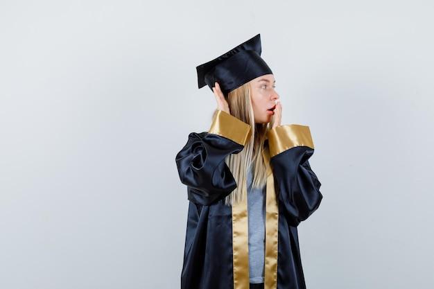 Fille blonde couvrant la bouche avec la main, tenant la main près de l'oreille pour entendre quelque chose en robe de graduation