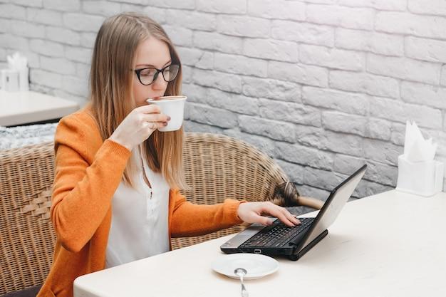 Fille blonde dans un café avec un ordinateur portable et une tasse de café. pigiste jeune fille travaillant sur un ordinateur portable