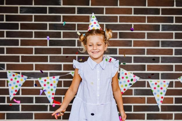 Une fille blonde dans un chapeau de papier festif rit et jette des bonbons sur le patio contre un mur de briques avec des drapeaux à pois.