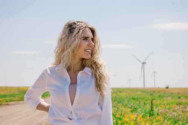 Une fille blonde dans une chemise blanche se dresse dans le vent dans un champ sur fond de moulins à vent