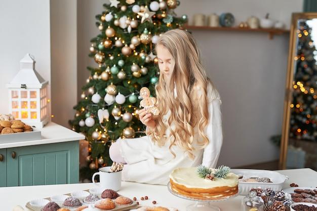 Fille blonde dans la cuisine du nouvel an avec des petits gâteaux et des bonbons