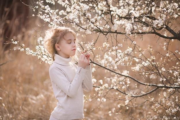 Fille blonde dans le jardin de fleurs. fond de printemps avec une fleur blanche