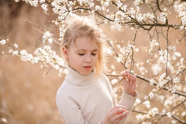 Fille blonde dans le jardin de fleurs.