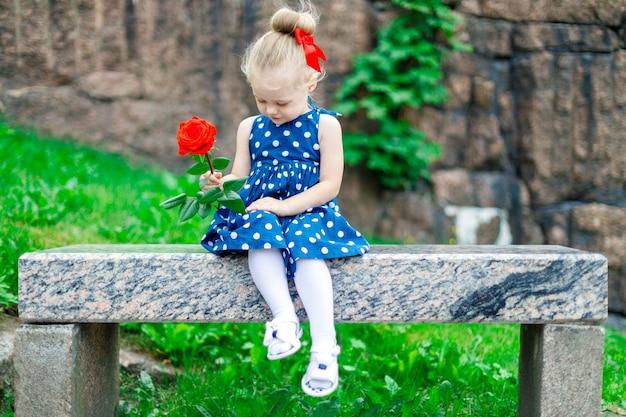 Fille blonde dans le parc est assise sur un banc avec une rose